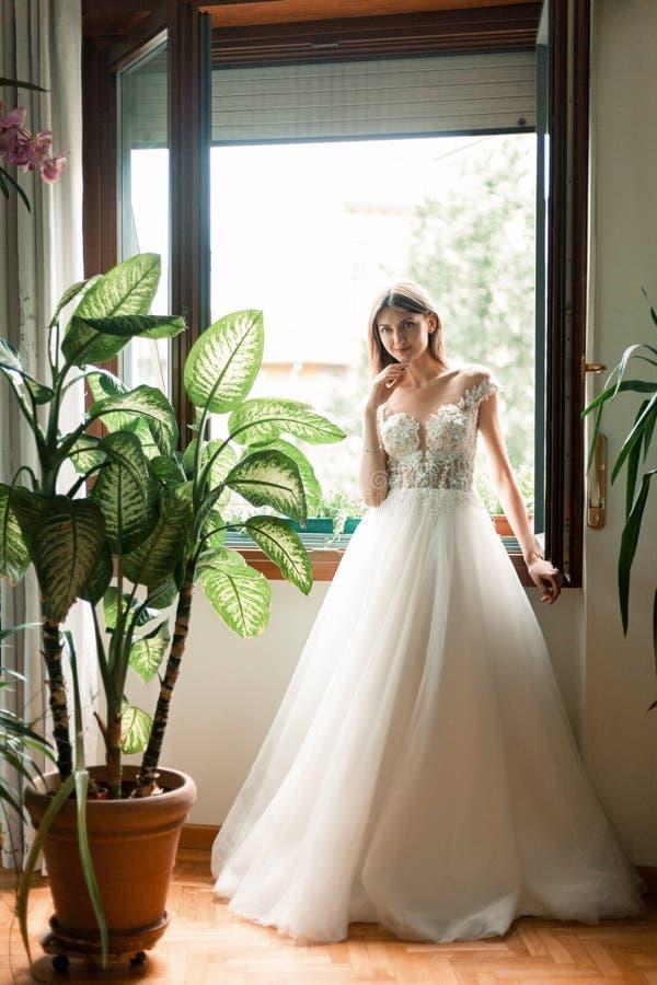 La novia se coloca cerca de una ventana abierta en su vestido de boda foto de archivo