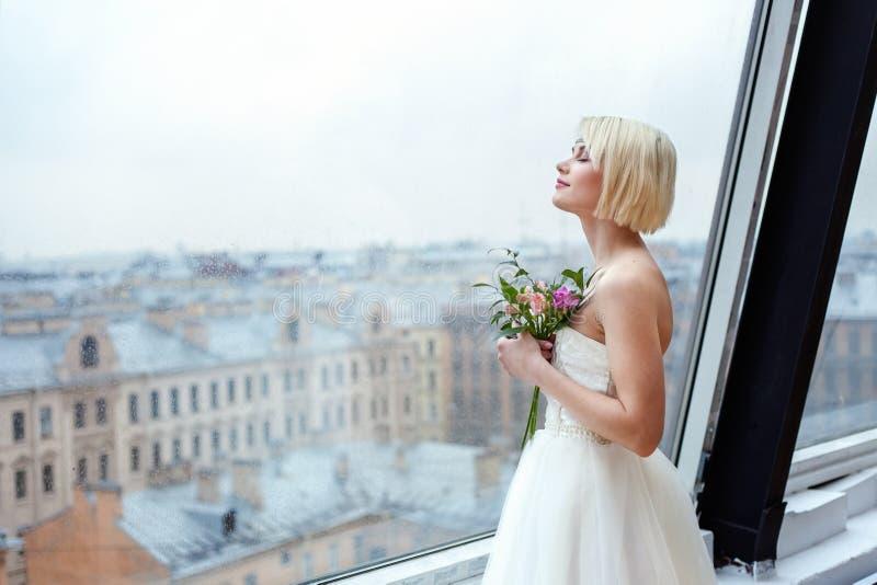 La novia se coloca en la ventana imágenes de archivo libres de regalías