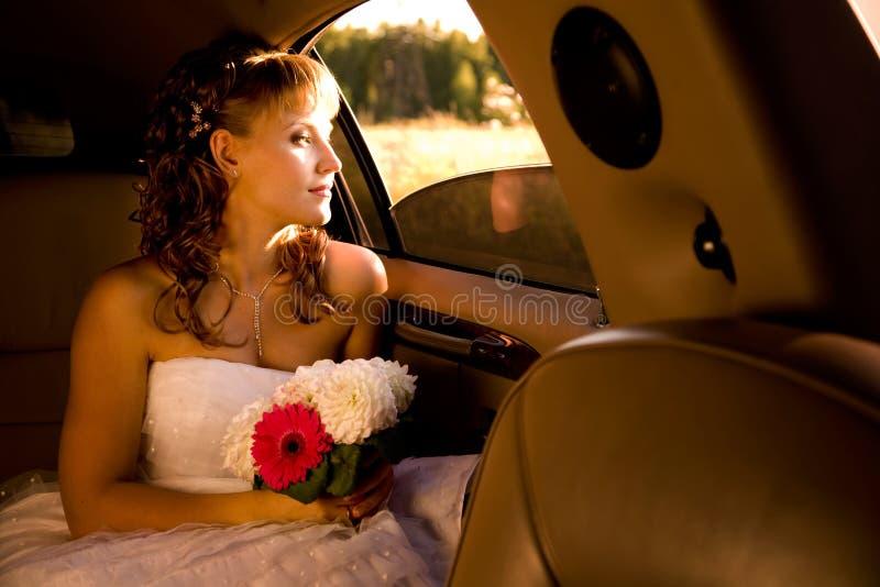 La novia se está sentando en limusina imagen de archivo