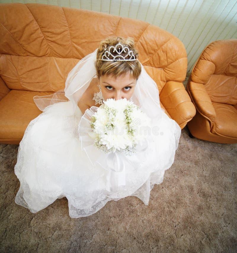 La novia se sienta en el sofá de cuero foto de archivo