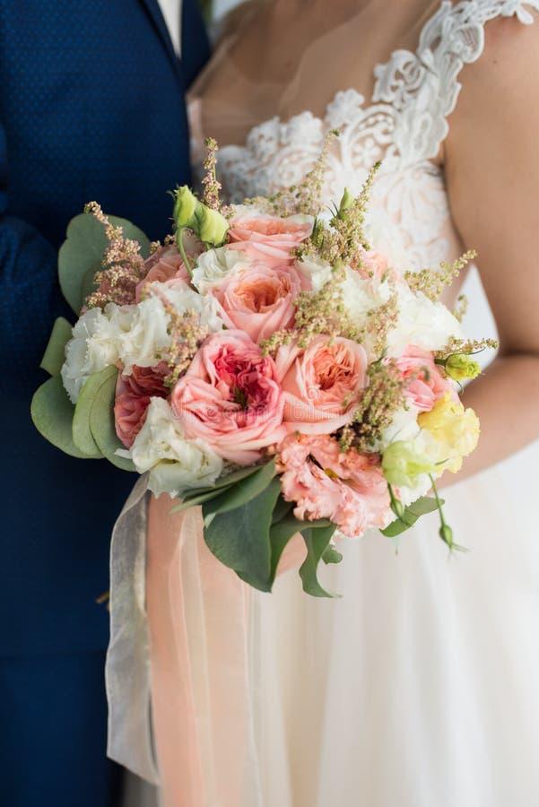 La novia se sostiene en sus manos que se casa el ramo con las rosas anaranjadas Ramo nupcial en formas en colores pastel imagen de archivo