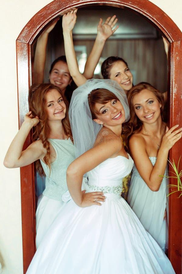 La novia sonríe amplio mientras que presenta en la puerta con las damas de honor foto de archivo libre de regalías