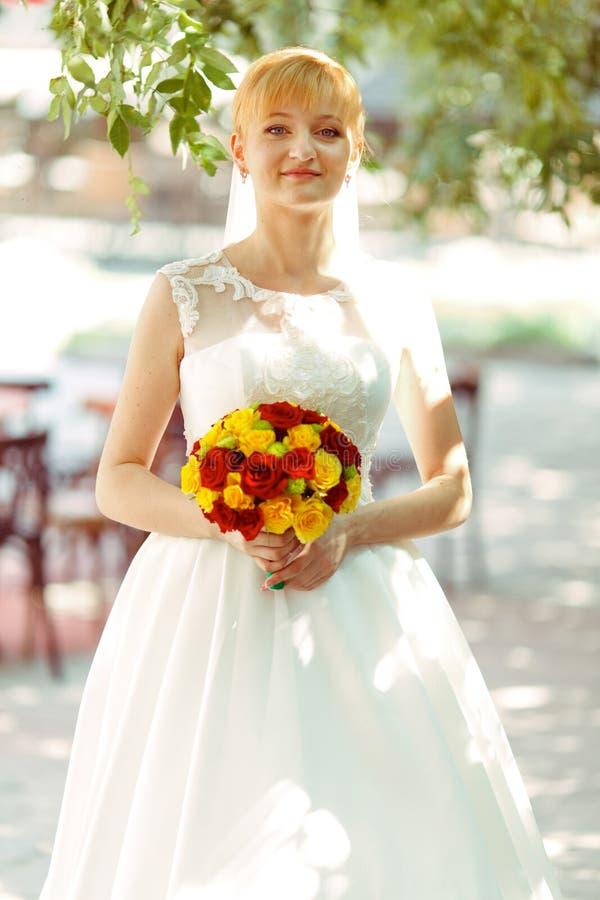 La novia sonríe colocándose con un bouqet en una calle por mañana brillante imágenes de archivo libres de regalías