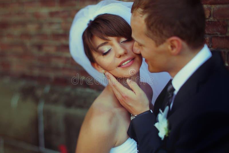 La novia sonríe con los ojos cerrados mientras que el novio toca su cara delic foto de archivo libre de regalías