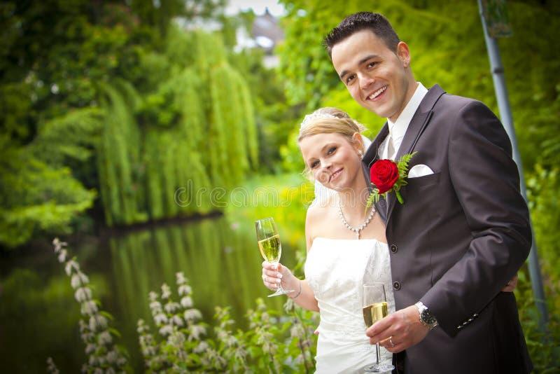 La novia sonriente con el novio está bebiendo el champán del vino espumoso imagen de archivo