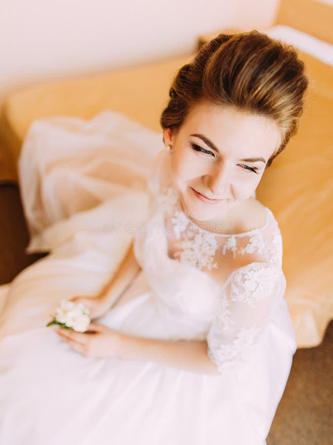 La novia sonriente está sosteniendo el mini-ramo blanco y se está sentando en la cama El retrato antedicho foto de archivo libre de regalías