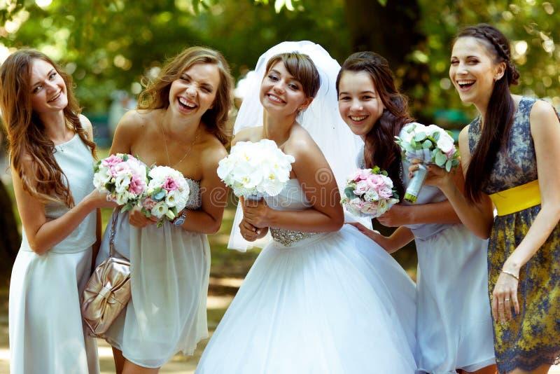La novia sonriente presenta con las damas de honor felices con los bouqets en su fotografía de archivo