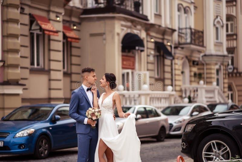 La novia sostiene al novio por la cara imagenes de archivo