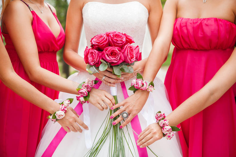 La novia sostiene el ramo de la rosa del rosa en manos bridesmaid imágenes de archivo libres de regalías