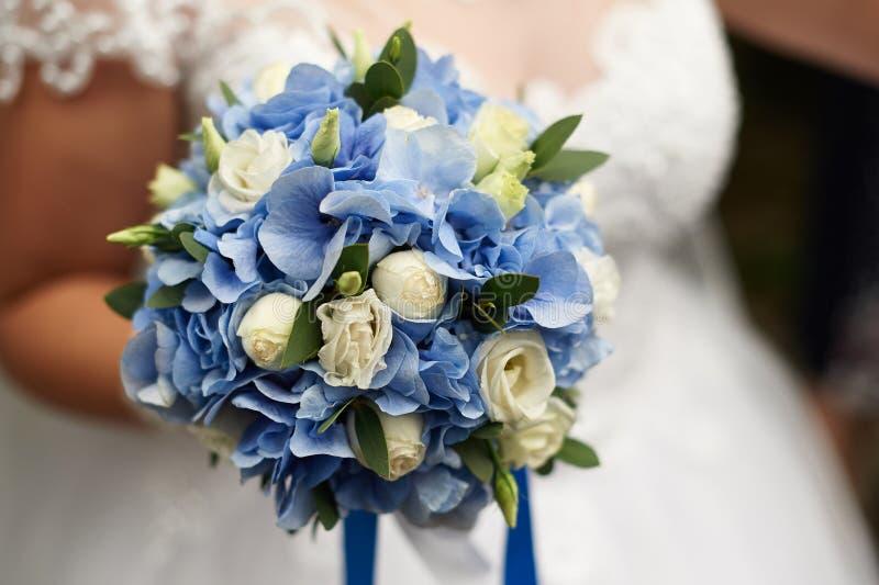 La novia sostiene en su mano un ramo que se casa hermoso de rosas y de hortensias azules imagen de archivo libre de regalías