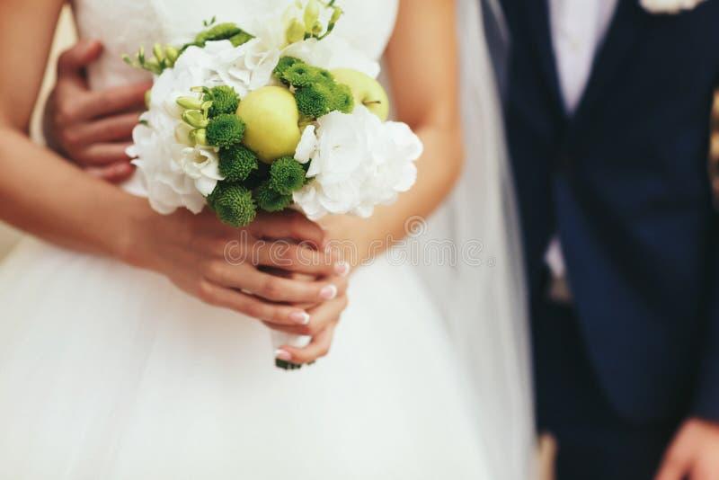 La novia sostiene en sus manos de la oferta un poco ramo de la boda hecho de fotografía de archivo libre de regalías