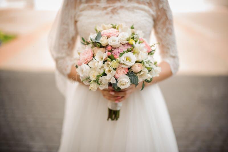 La novia sostiene un ramo blando de la boda en sus manos fotografía de archivo
