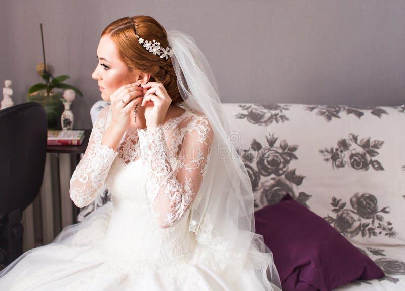 La novia toma los pendientes, casandose la preparación fotografía de archivo libre de regalías