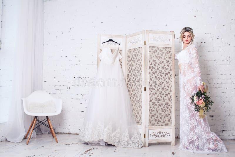 La novia, vestida en peignoir y ropa interior, coloca el escudo cercano con el vestido de boda y sostiene el ramo en sus manos foto de archivo libre de regalías