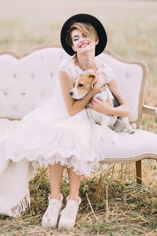 La novia vintage-vestida sonriente con el sombrero negro está abrazando el perro precioso y se está sentando en el sofá en el sol fotografía de archivo libre de regalías