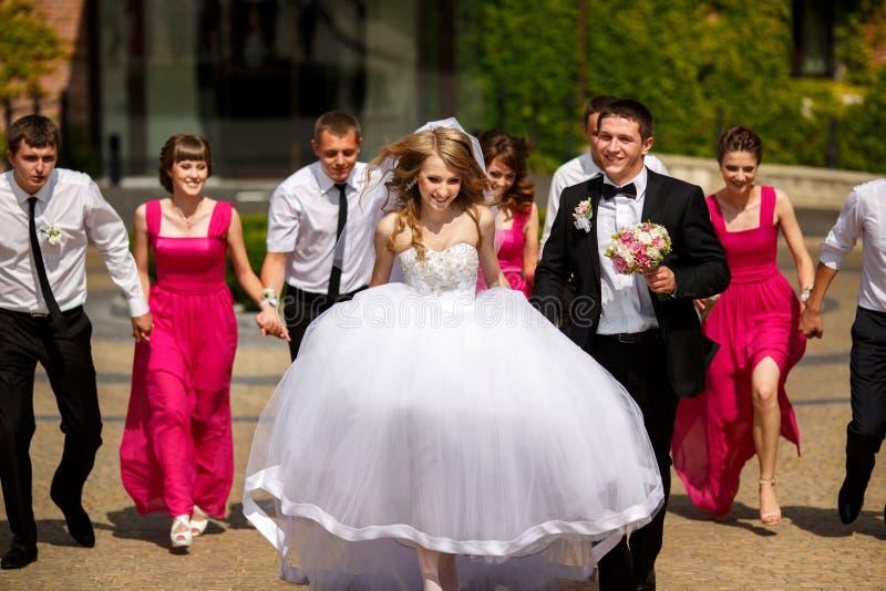 La novia y el novio caminan en el parque que es seguido por sus amigos fotografía de archivo libre de regalías