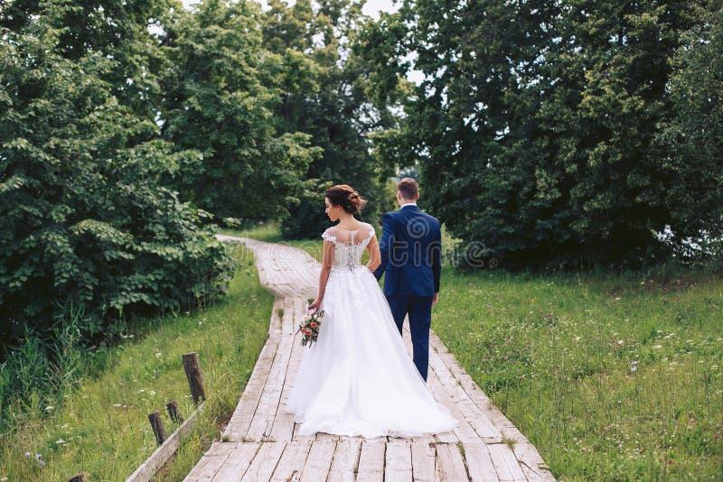 La novia y el novio caminan a lo largo de una trayectoria de madera entre los árboles en el parque fotografía de archivo libre de regalías