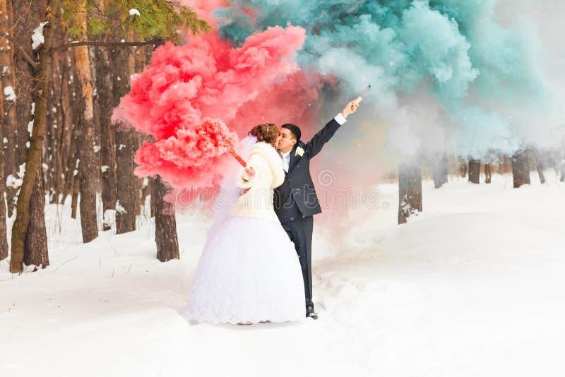 La novia y el novio con las bombas de humo en invierno fotos de archivo