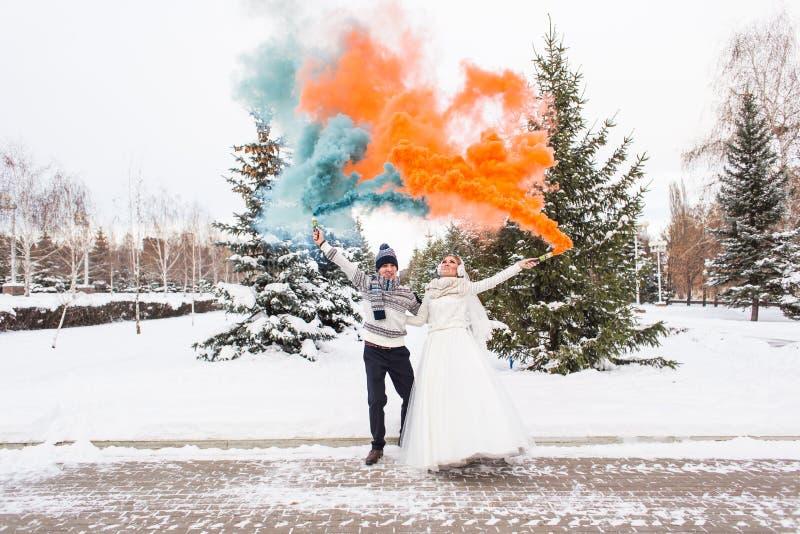 La novia y el novio con las bombas de humo en invierno fotografía de archivo