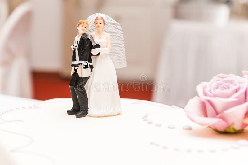 La novia y el novio divertidos hicieron del azúcar encima del pastel de bodas foto de archivo