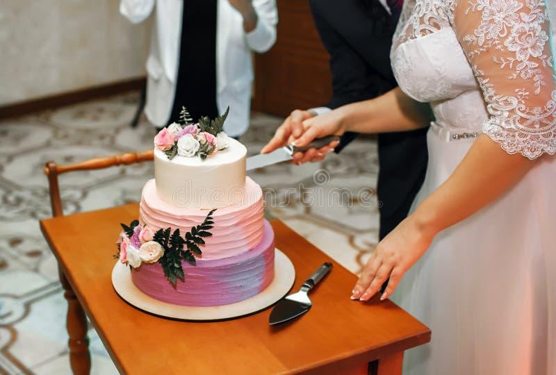 La novia y el novio en la boda cortaron el pastel de bodas, la torta se adorna con las flores fotos de archivo libres de regalías
