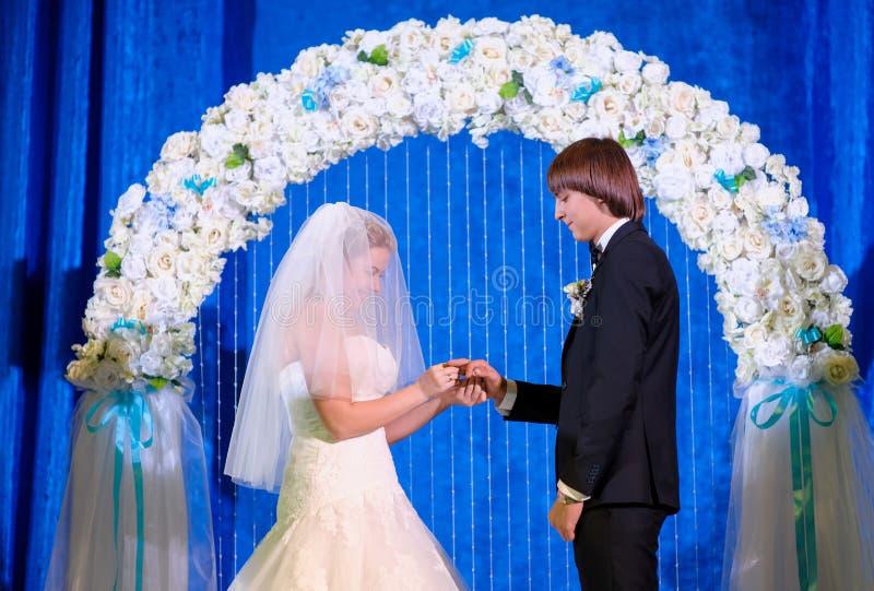 La novia y el novio en el arco llevan los anillos de bodas imagen de archivo libre de regalías