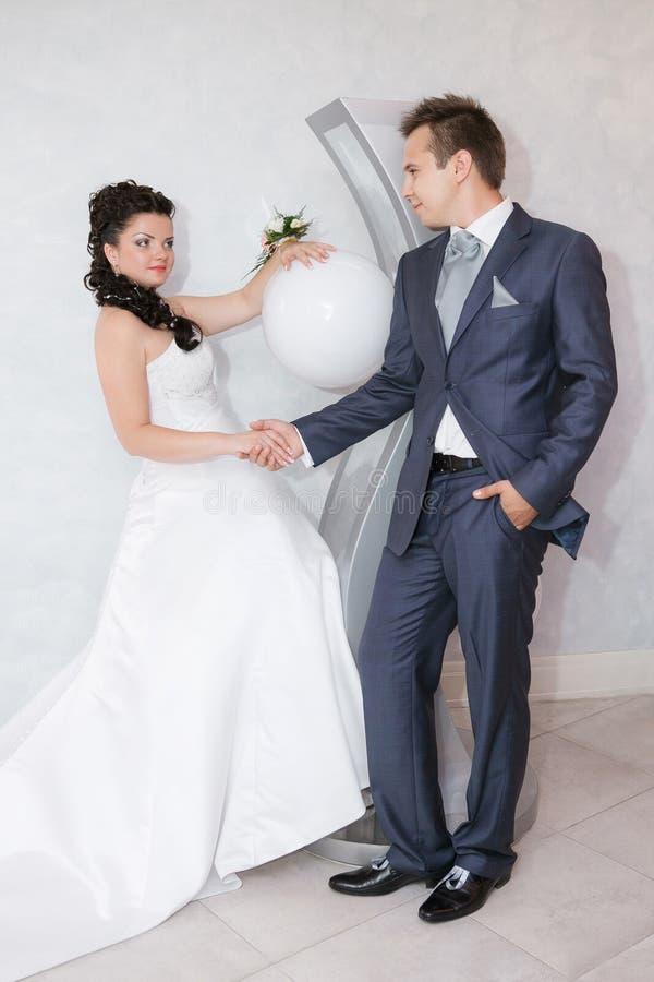 la novia y el novio en la boda caminan en el pasillo moderno del hotel foto de archivo libre de regalías