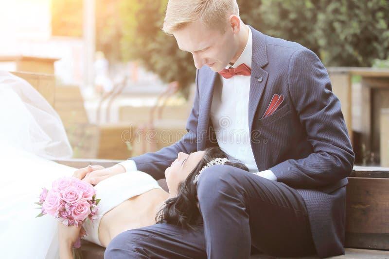 La novia y el novio en un banco en la ciudad parquean fotografía de archivo libre de regalías