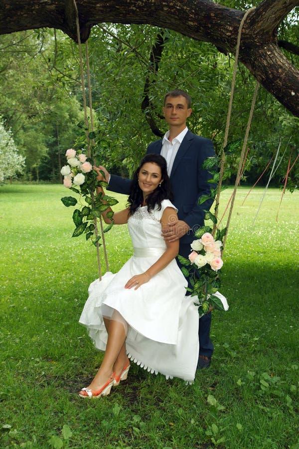 La novia y el novio en una sesión fotográfica en un parque con un árbol balancean foto de archivo