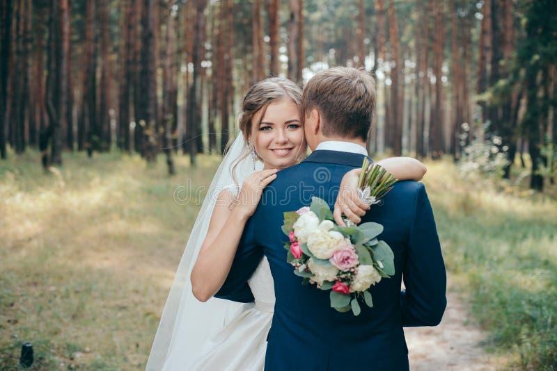 La novia y el novio en vestidos de boda en fondo natural Día de boda Los recienes casados están caminando a través del bosque fotografía de archivo