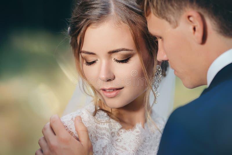 La novia y el novio en vestidos de boda en fondo natural El par joven imponente es increíblemente feliz Día de boda foto de archivo libre de regalías