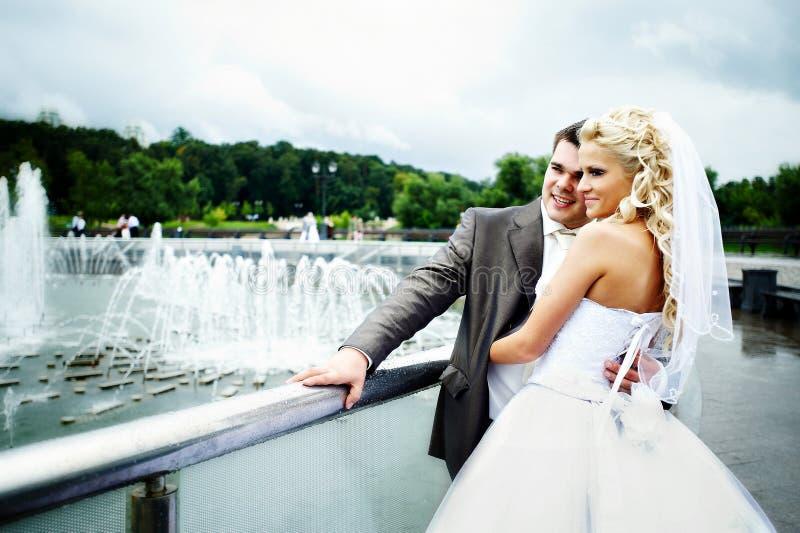 La novia y el novio felices en la boda recorren en el puente fotografía de archivo