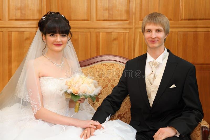 La novia y el novio felices se sientan en el sofá fotografía de archivo