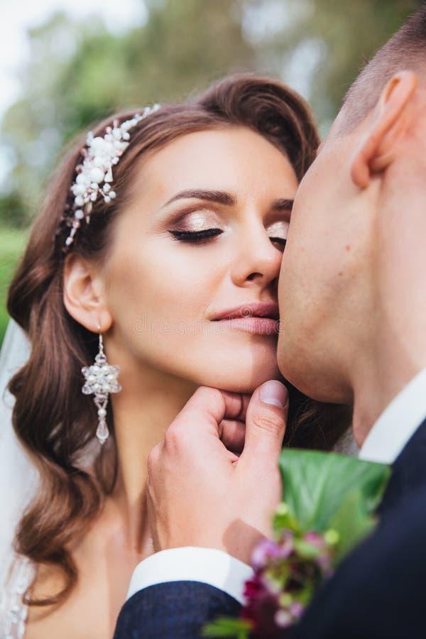 La novia y el novio hermosos del recién casado en parque hacen frente al primer imagenes de archivo