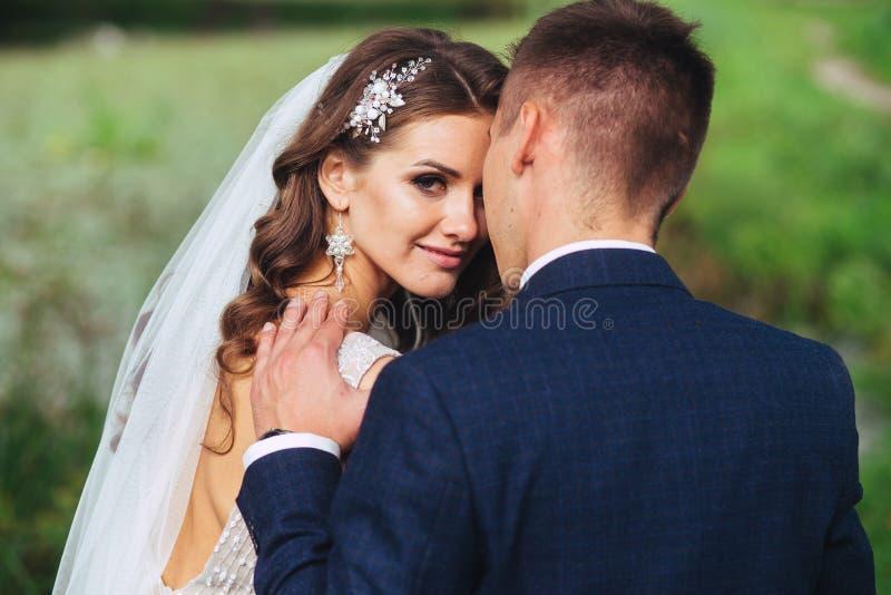 La novia y el novio hermosos del recién casado en parque hacen frente al primer foto de archivo