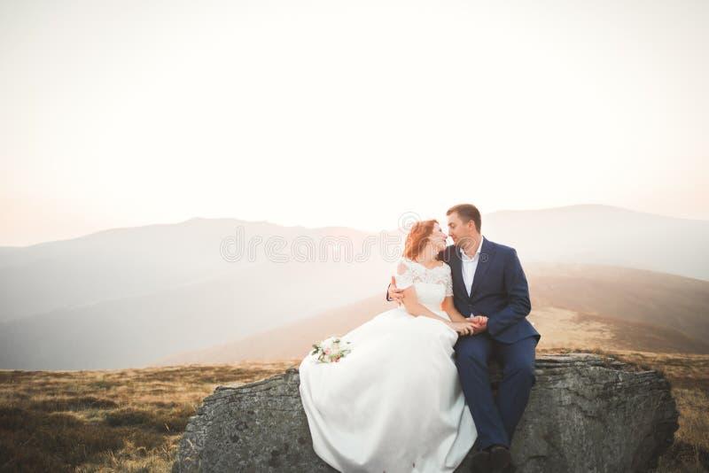 La novia y el novio hermosos felices de los pares de la boda en el día de boda al aire libre en las montañas oscilan Pares de la  fotos de archivo