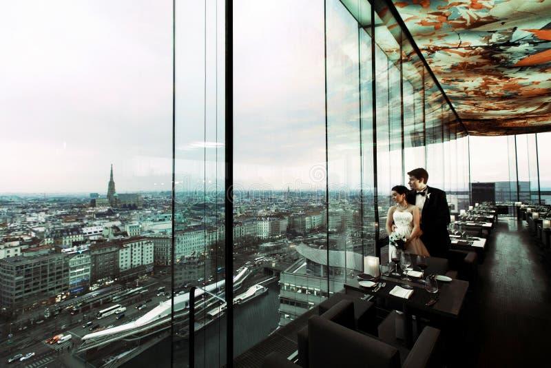 La novia y el novio miran el gran paisaje urbano que se coloca detrás de un PA foto de archivo