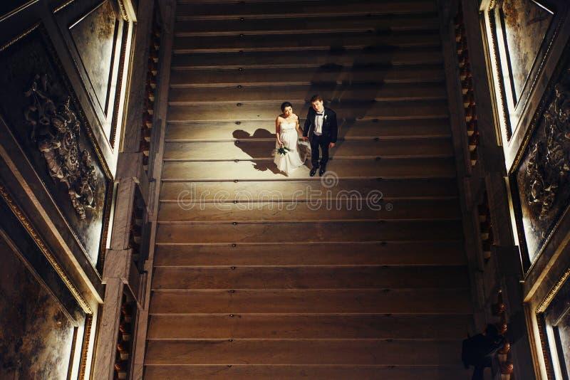 La novia y el novio miran que se levantan en las escaleras en el viejo teatro ha foto de archivo