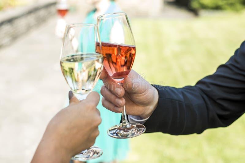La novia y el novio que celebran maravillosamente casarse los vidrios con el vino espumoso del chamán tuestan foto de archivo libre de regalías