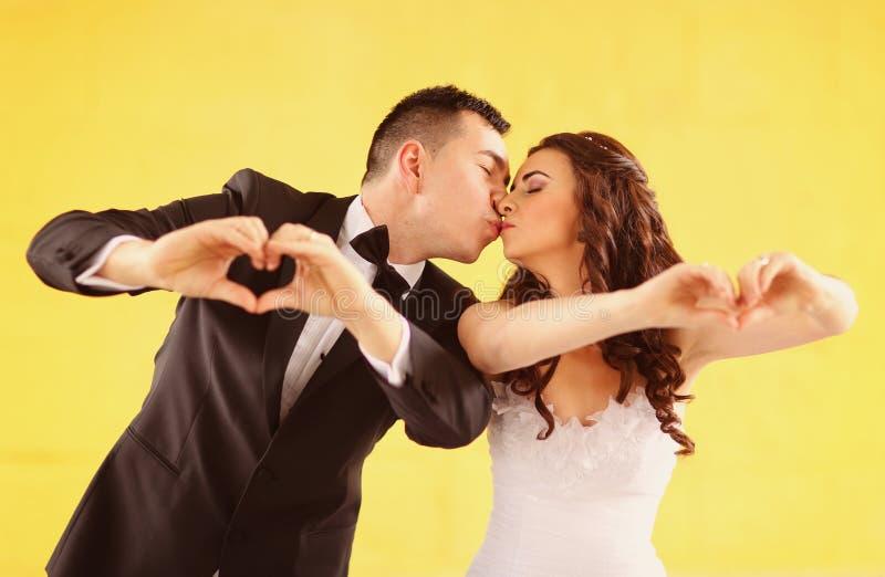 La novia y el novio que hacen el corazón forman con sus manos foto de archivo libre de regalías