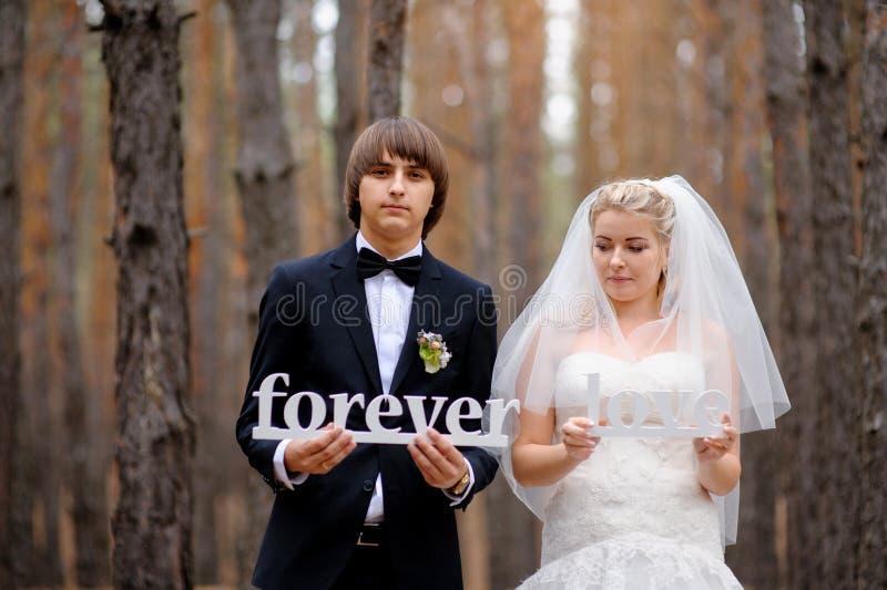 La novia y el novio que llevan a cabo letras de madera aman para siempre fotos de archivo libres de regalías
