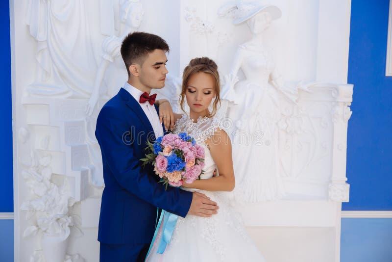 La novia y el novio que presentan contra una pared escultural blanca Blonde hermoso en un vestido de boda con un ramo rosado-azul foto de archivo libre de regalías
