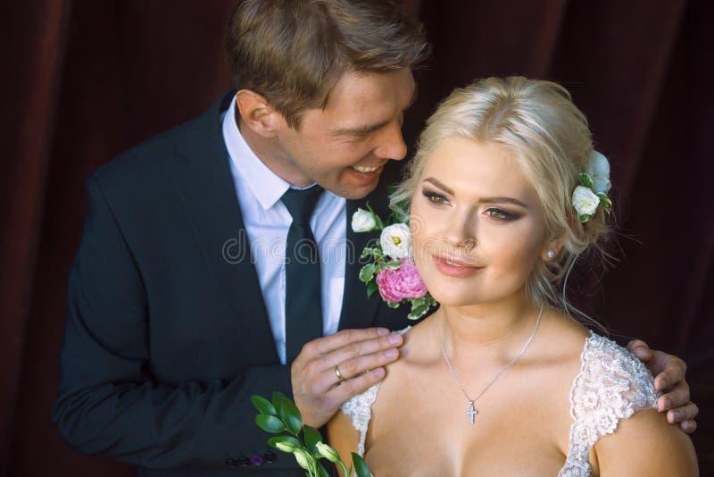 La novia y el novio se colocan de lado a lado imágenes de archivo libres de regalías