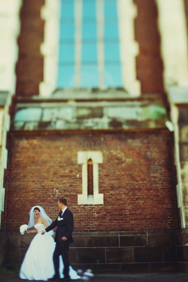 La novia y el novio se colocan debajo de una ventana grande de una catedral vieja foto de archivo