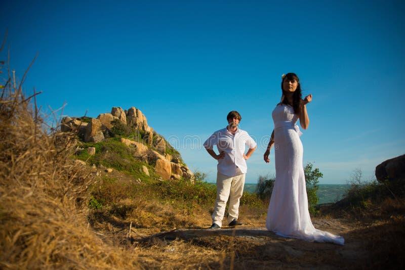 La novia y el novio se colocan en el fondo de montañas y del cielo fotografía de archivo