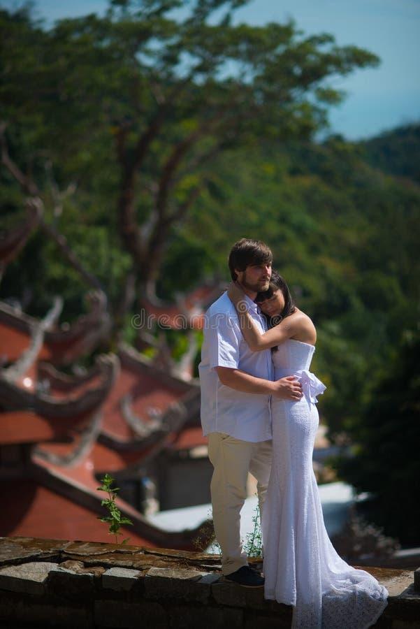 La novia y el novio se colocan en el fondo del templo vietnamita viejo foto de archivo