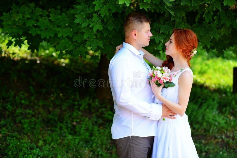 La novia y el novio se detienen las manos mientras que caminan a lo largo de fotos de archivo