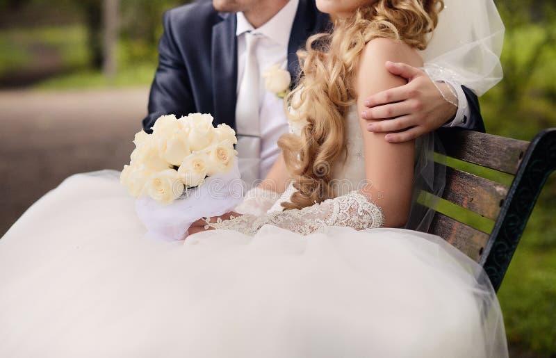 La novia y el novio se están sentando en el parque en un banco Él embra foto de archivo