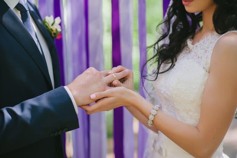 La novia y el novio se llevan en una ceremonia de boda cuando los anillos en un fondo de cintas multicoloras, amor, boda, rel foto de archivo
