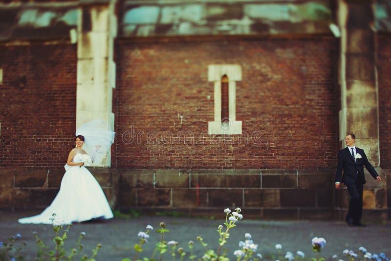 La novia y el novio se mantienen aparte detrás de un mundo viejo del ladrillo imagenes de archivo